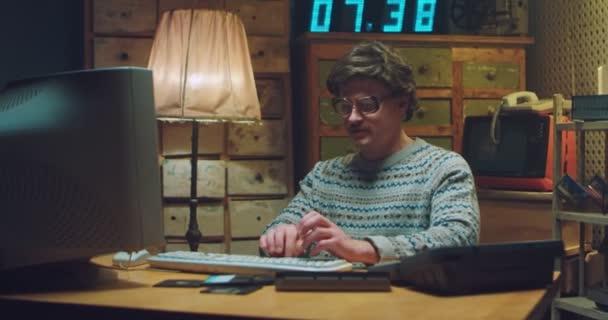 Kavkazský nervózní mužský šprt v brýlích s knírkem, který sedí za stolem v retro místnosti, pracuje na počítači a má problémy. Muž programátor psaní na klávesnici a selhání. Klasika ročníku. Chyba. Selhání