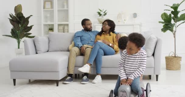 Nette kleine afroamerikanische Kinder, die im Wohnzimmer spielen. Mutter und Vater sitzen in Umarmungen auf der Couch im Hintergrund. Kleiner Junge reitet hübsches Mädchen auf Spielzeugauto. Zu Hause. Familie zusammen.