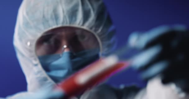 Close up of Caucasian male doctor in full protection, mask and goggles holding glass tube with blood. Positive test for covid-19 in laboratory. Coronavirus vaccine inventing.