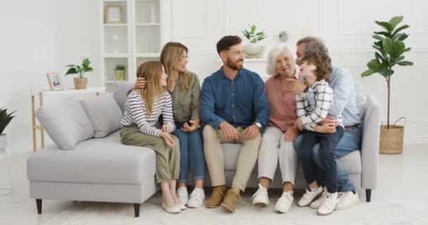 Velká bělošská rodina sedí na gauči v obývacím pokoji a komunikuje. Prarodiče, rodiče a malé děti jsou doma pod zámkem. Děti mluví s matkou, otcem, babičkou a dědečkem.