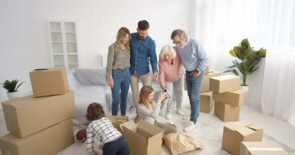 Caucasian parents and grandparents in living room with small cute kids unpacking carton boxes. Family with children and elderly moving in new house after repairment. Replacing in new apartment.