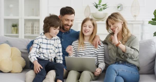 Kavkazská mladá rodina se dvěma dětmi sedícími na gauči v obývacím pokoji a používajícími notebook. Matka, otec, syn a dcera poklepávají, šplhají a dívají se na něco online. Doma.