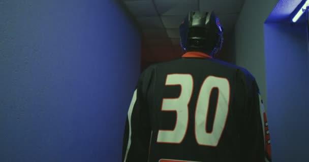 Hinten ein männlicher Eishockeyspieler in Uniform mit der Nummer 30 und Helm, der durch einen schmalen Korridor zur Arena läuft. Rückansicht des Sportlers, der über die Landebahn zum Spielort fährt.