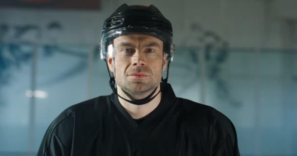 Portrétní snímek pohledného mladého bělocha mužského hokejisty v helmě, jak se dívá na kameru se zlověstnou tváří na ledové aréně. Zblízka atraktivní sportovec v casque.
