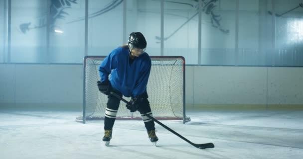 Portrét kavkazské krásné koncentrované ženské hokejistky v uniformě a helmě stojící na ledové aréně s kyjem a pukem. Hezká sportovkyně v casque s tyčinkou a diskem na ledovém povrchu.