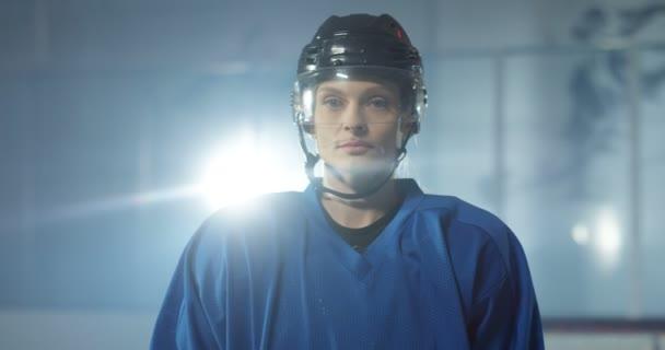Portrét záběru vážně krásné mladé bělošky hokejistky v helmě dívající se na kameru na ledové aréně. Zblízka atraktivní sportovkyně v casque ve světle reflektorů.