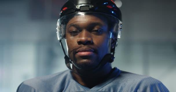 Detailní záběr šťastný mladý afroameričan hokejista v helmě vesele se usmívá a dýchá párou na ledové aréně. Portrét radostného sportovce.