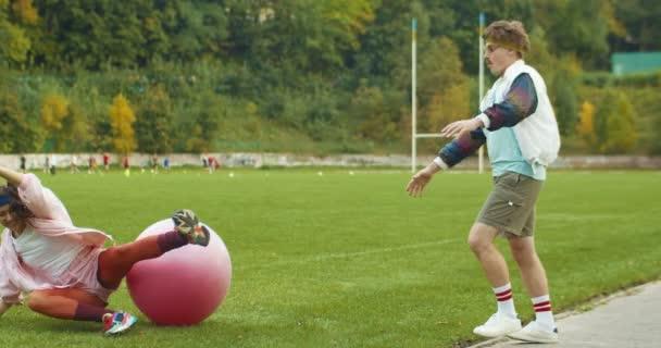 Lustige fröhliche kaukasische hübsche Vintage-Athletin, die im Freien auf Fitnessball springt und auf den Boden fällt. Männlicher Fitnesstrainer mit Schnurrbart hilft ihr. Sportlicher Lebensstil. Retro-Konzept