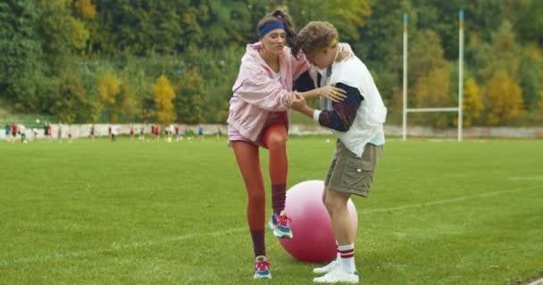 Schöne lustige kaukasische Fitnesstrainerin, die der schönen altmodischen Vintage-Sportlerin hilft, die sich beim Training mit Fitnessball am Bein verletzt hat. 60er Jahre Sport Lifestyle. Retro-Konzept.