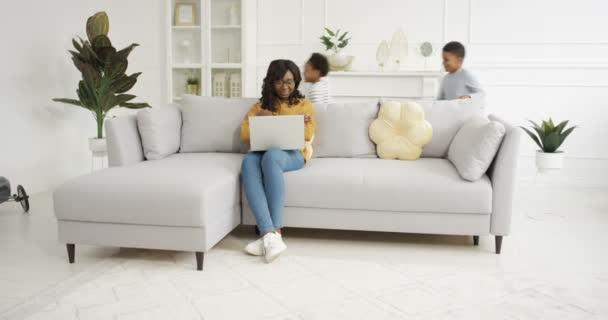 Dvě radostné afroamerické děti pobíhající v kruzích a kruzích v obýváku. Šťastný roztomilý malý chlapec a dívka hrající si kolem pohovky. Usmála se matka sedí na gauči, pracuje na notebooku doma