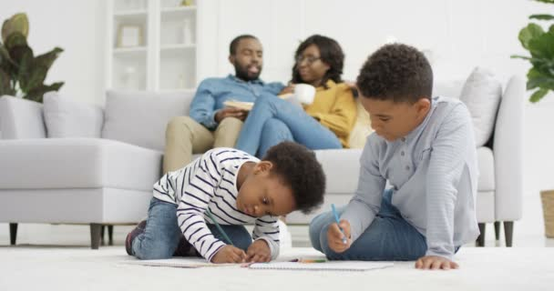 African American happy kids sitting on floor and coloring picture with pencils. Small sister and brother playing at home. Parents sitting on couch and talking on background. Mother and father resting.