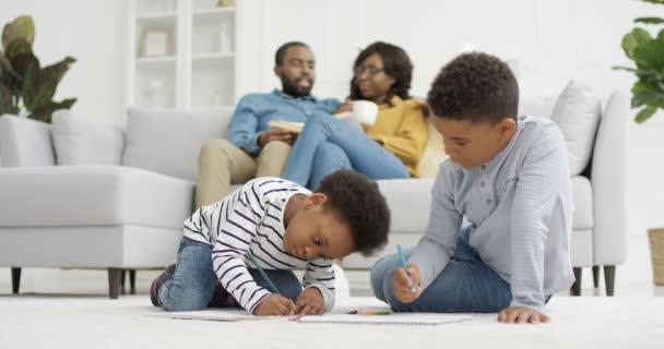 Afroameričtí šťastné děti sedí na podlaze a maluje obrázek s tužkami. Malá sestra a bratr si hrají doma. Rodiče sedí na gauči a mluví v pozadí. Matka a otec odpočívají.