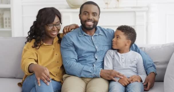 Portrét mladé šťastné afroamerické rodiny s roztomilým malým synem. Malý chlapec sedí na pohovce v obývacím pokoji s rodiči a radostně se usmívá. Matka a otec čeká dítě na gauči doma.