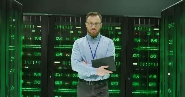 Kaukasischer gutaussehender junger Mann mit Brille, der zwischen Servern mit Big-Data-Informationen wandelt und ein Tablet in der Hand hält. Grün arbeitende Prozessoren im Datenbankspeicher Gut aussehende männliche Analytiker im Rechenzentrum