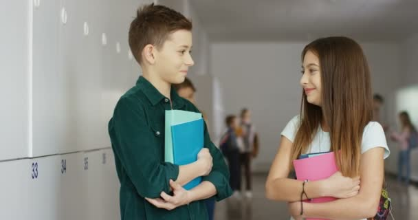 Caucasian teenage friendly boy and girl standing together in the school corridor during a break, looking at each other and then smiling joyfully to the camera. Portrait shot.