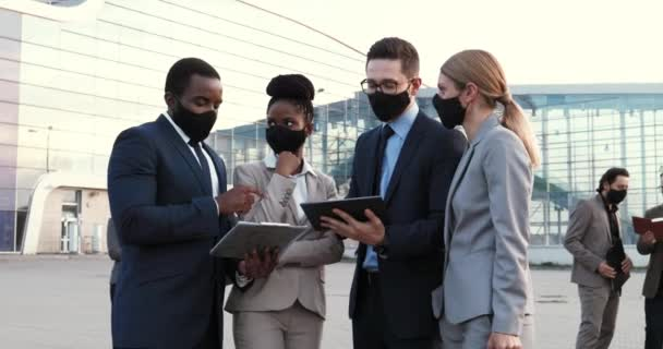 Mixed-races males females business partners in masks talking and using tablet device and documents outdoor. Multi ethnic businessman and businesswoman having conversation at meeting in city. Pandemic.