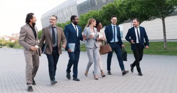 Ein gemischtes Team erfolgreicher Männer und Frauen im Business-Stil, die im Freien spazieren gehen und fröhlich miteinander reden. Multi-ethnisch glückliche Geschäftsleute und Geschäftsfrauen, die auf der Straße flanieren und kommunizieren.