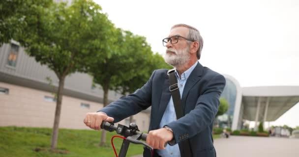 Portrét bělocha s šedivými vlasy a brýlemi sedícího na kole a hledícího do kamery. Starší šedovlasý dědeček na elektrickém skútru venku. Muž důchodce na kole ve městě.