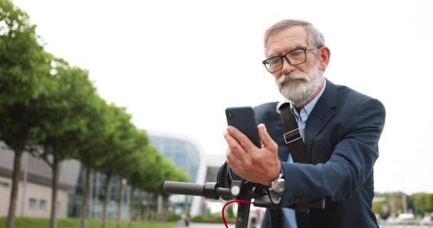 Starší šedovlasý muž v brýlích a sluchátkách, stojící na kole na ulici a poklepávající nebo posouvající se po mobilním telefonu. Starý dědeček v brýlích pomocí smartphone a prohlížení online venkovní.