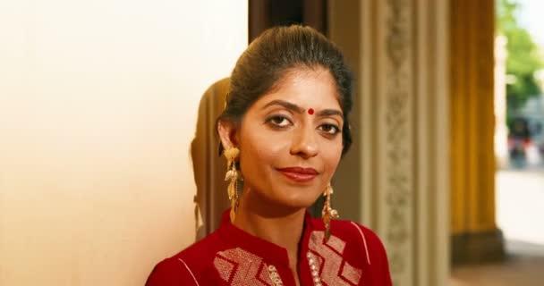 Portraitaufnahme von Hindu junge stilvolle schöne Frau mit Punkt auf der Stirn und in traditioneller Kleidung, die freudig in die Kamera lächelt. Draußen. Nahaufnahme eines hübsch lächelnden glücklichen Mädchens aus Indien.