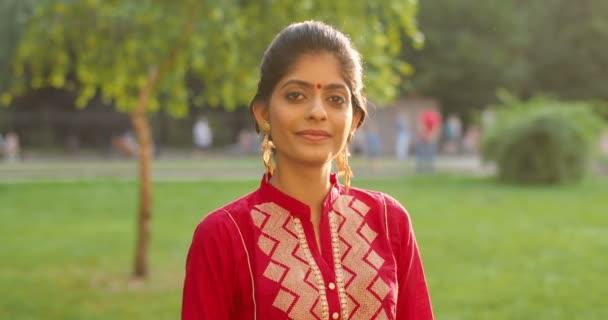 Porträt einer hinduistischen jungen schönen Frau mit Punkt auf der Stirn und in traditionellem Outfit, die in die Kamera lächelt und den Daumen hebt. Draußen im Park. Nahaufnahme eines hübsch lächelnden glücklichen Mädchens aus Indien.