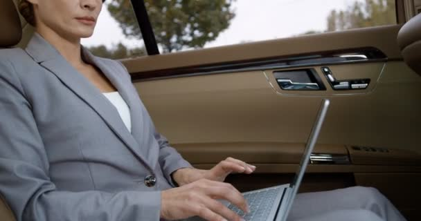 Kaukasische Geschäftsfrau sitzt auf dem Rücksitz des Autos und arbeitet am Laptop. Schöne Frau tippt auf der Tastatur, während sie zur Arbeit geht. Umtriebige reiche Unternehmerin schreibt E-Mail über das Büro.