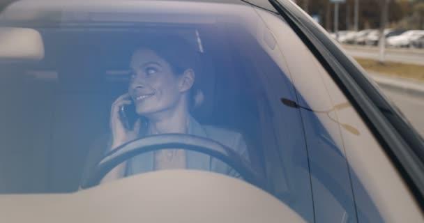 Schöne junge kaukasische fröhliche Frau sitzt am Steuer und spricht auf dem Smartphone. Hübsch lächelnde Autofahrerin, die am Handy spricht und lacht. Blick durch Windschutzscheibe.