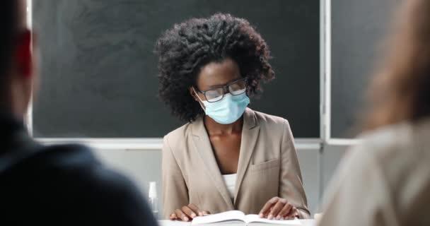 Fiatal afro-amerikai tanárnő szemüvegben és orvosi maszkban ül az asztalnál az iskolában, tankönyvet olvas és tanít. Irodalmi lecke. Női oktató diákok vagy tanulók előtt.
