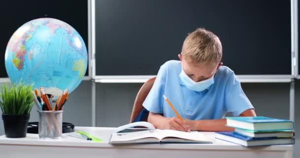 Malý kavkazský chlapec v lékařské masce sedí za stolem se světovou zeměkoulí ve škole. Teenage školák dělá domácí úkoly a psaní cvičení v sešitu. Učení žáků ve třídě. Koncept koronaviru