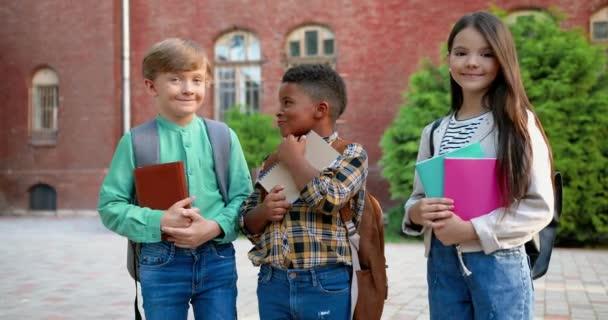 Fröhliche Mixed-Rennen männliche und weibliche Schüler mit Textbüchern in den Händen, die vor der Schule stehen. Hübsches kaukasisches Mädchen, das draußen lächelt. Ein süßer afroamerikanischer Junge in guter Laune. Schülerkonzept