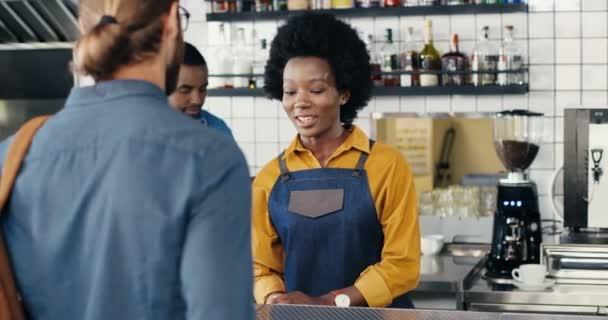 Csinos mosolygós afro-amerikai csapos lány, aki a kaukázusi pasastól kapott parancsokat. Egy férfi ügyfél háta mögött. Vegyes fajták. A vendég kávét vesz és pincérnővel beszél a kávézóban. Többnemzetiségű.