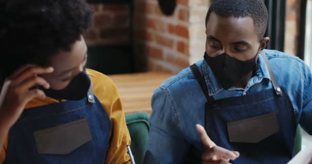 Close up of African American couple in masks doing business calculations and checking bills. Calculating spends and damages. Reopen after quarantine. Counting at laptop computer Small entrepreneurship