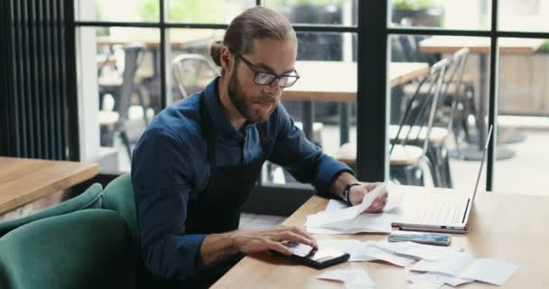 Caucasian young man sitting at table and doing business calculations. Man in glasses calculating spends and damages of cafe. Reopen after lockdown. Counting at laptop computer. Small entrepreneurship.