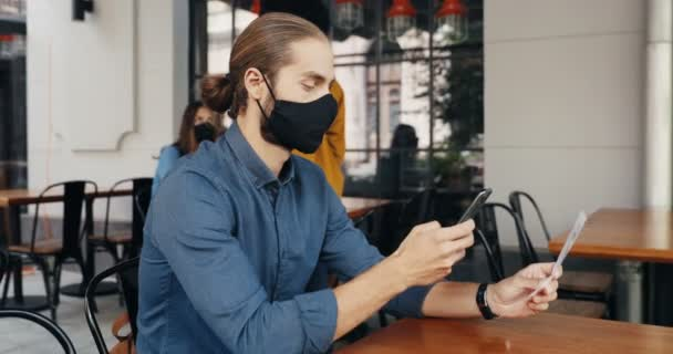 Běloch muž klient v masce sedí u stolu v kavárně venkovní a skenování QR kód s smartphonem pro čtení menu. Technologie během pandemie covid-19. Muž zákazník v baru, aby objednávky na telefonu.