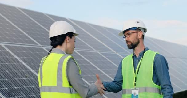 Dva inženýři: žena a muž ve speciální uniformě s bílými přilbami potřásající si rukama na pozadí solárního panelu.