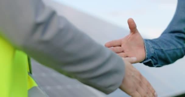 Zavřít stisk ruky na pozadí solárního panelu venku. Ženský inženýr si se souhlasem partnera potřásá rukou.