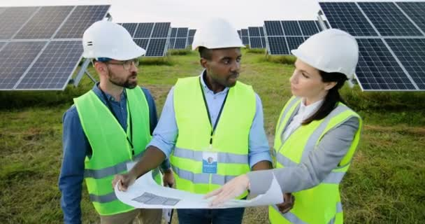 Camera moves away from three engineers in special uniform standing on farm with solar panels. Woman and two men looking at layout of objects.