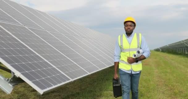Porträt eines glücklichen afrikanisch-amerikanischen Solarkraftwerksarbeiters, der Papierrollen mit Diagrammen und Werkzeugkiste trägt.