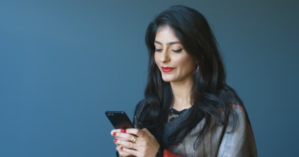 Beautiful cheerful Hindu young woman in traditional outfit texting message on smartphone and chatting. Attractive female tapping and typing on mobile phone while smiling joyfully.