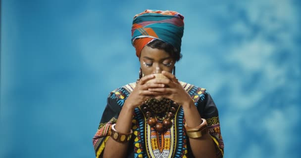 African American young beautiful woman in traditional clothes drinking hot tea and enjoying its taste. Good looking stylish pretty girl from Africa sipping herbal drink from cup.