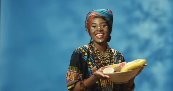 Portrét mladé Afroameričanky krásné ženy v tarditním oblečení, vesele se usmívající na kameru a držící talíř s ovocem v rukou. Vítejte v Africe. Šťastná dívka tančí s ovocem.