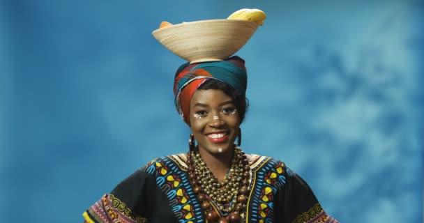 A fiatal afro-amerikai gyönyörű nő portréja késői ruhában, vidáman mosolyog a kamerába, és gyümölcsös tányért tart a fején. Üdv Afrika koncepciójában. Boldog lány, gyümölcsös pózban.
