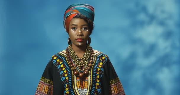 Portraitaufnahme einer attraktiven jungen Afroamerikanerin in traditionellem Outfit, die mit ernstem Gesicht in die Kamera blickt. Schöne stilvolle Frau in buntem Hemd auf blauem Wandhintergrund.