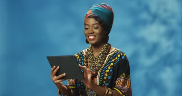 African American pretty woman in traditional clothes holding tablet device and tapping or scrolling. Attractice Indian girl typing on tablet computer. Female watching video online.