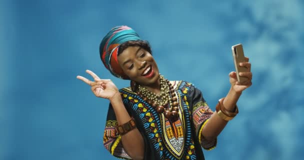 Stylish attractive African American young female in traditional outfit smiling joyfully and posing to smartphone camera and taking selfie photos. Beautiful woman making pictures with phone.