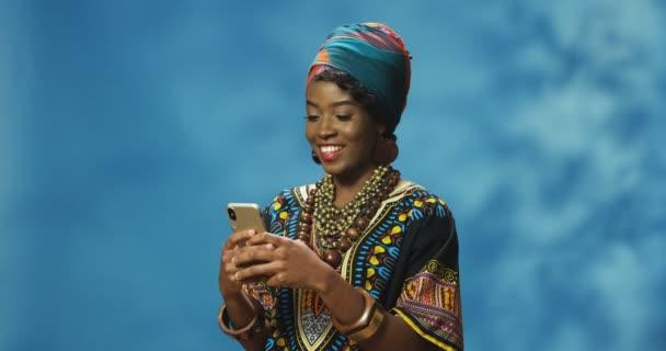 Schöne, fröhliche junge Afroamerikanerin in traditionellem Outfit, die SMS auf dem Smartphone versendet und sich unterhält. Attraktive Frauen tippen und tippen auf dem Handy und lächeln fröhlich.
