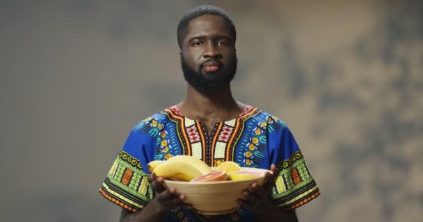 Portré fiatal vidám mosolygott jóképű afro-amerikai férfi átnyújtja és bemutató lemez trópusi gyümölcs és a kamerába néz. Vonzó srác, aki gyümölcsöt mutat és boldogan mosolyog..