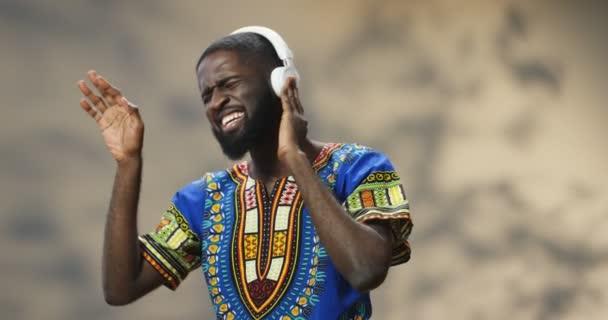 Afrikai-amerikai fiatal jóképű férfi szakállal és hagyományos ruhákban énekel és zenét hallgat fülhallgatóban. Guy élvezi kedvenc dalát.