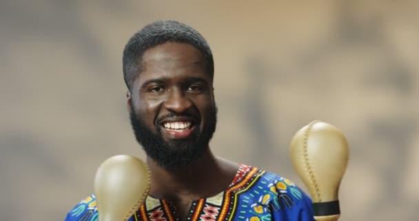 Egy jóképű afro-amerikai férfi portréja, aki vidáman mosolyog és maracán játszik. Közelkép boldog fickó kezében hangszerek és így rímmel a zene, miközben remeg.