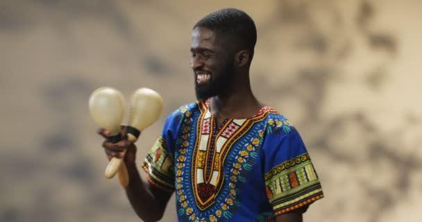 Portrét pohledného mladého Afroameričana v tradičním oblečení, vesele se usmívajícího a hrajícího na marakách. Šťastný chlap drží hudební nástroje a dělat rytmus na hudbu při třepání.